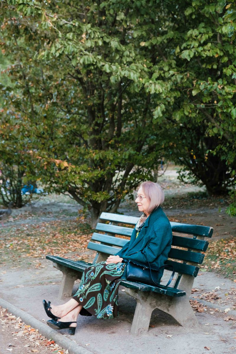 A woman sitting in a parc with autumn leaves
